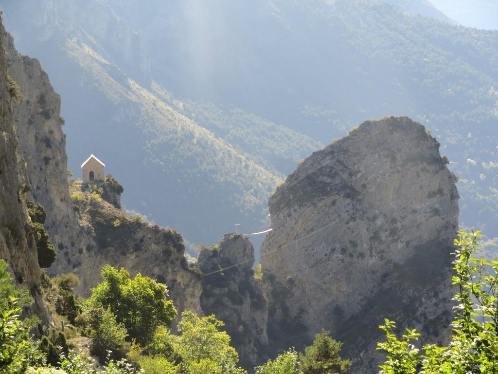 """In het midden van de foto een hangbrug die twee rotsen van de Via Ferrata met elkaar verbindt. Links op de foto het prachtige maar afgelegen kappelletje """"Sain-Sauveur"""""""