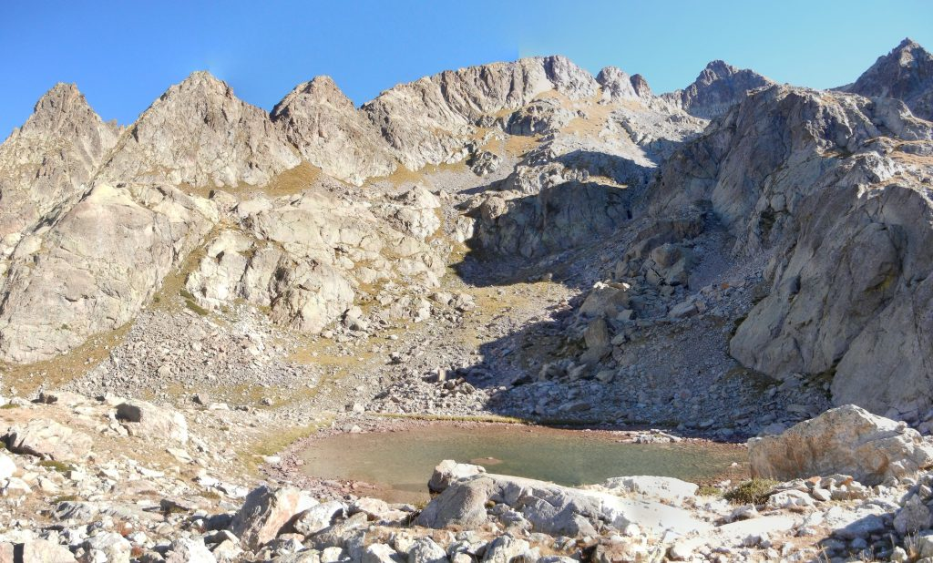 Het Lac du Mont Colomb is op 2390 meter op het vlak van oppervlakte niet echt om over naar huis te schrijven. Maar merk wel op dat men zich hier reeds volop tussen de rotsblokken bevindt.